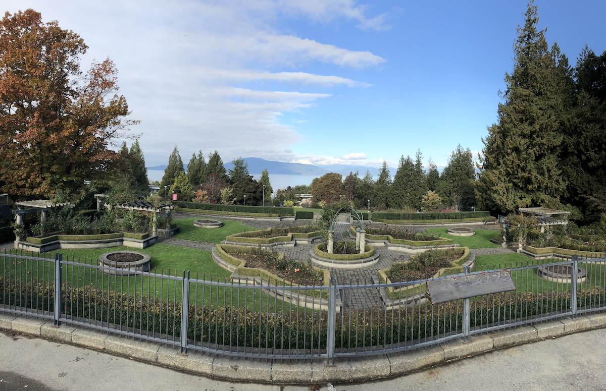 A panorama view over the UBC Rose Garden, with English Bay and the North Shore visible beyond.