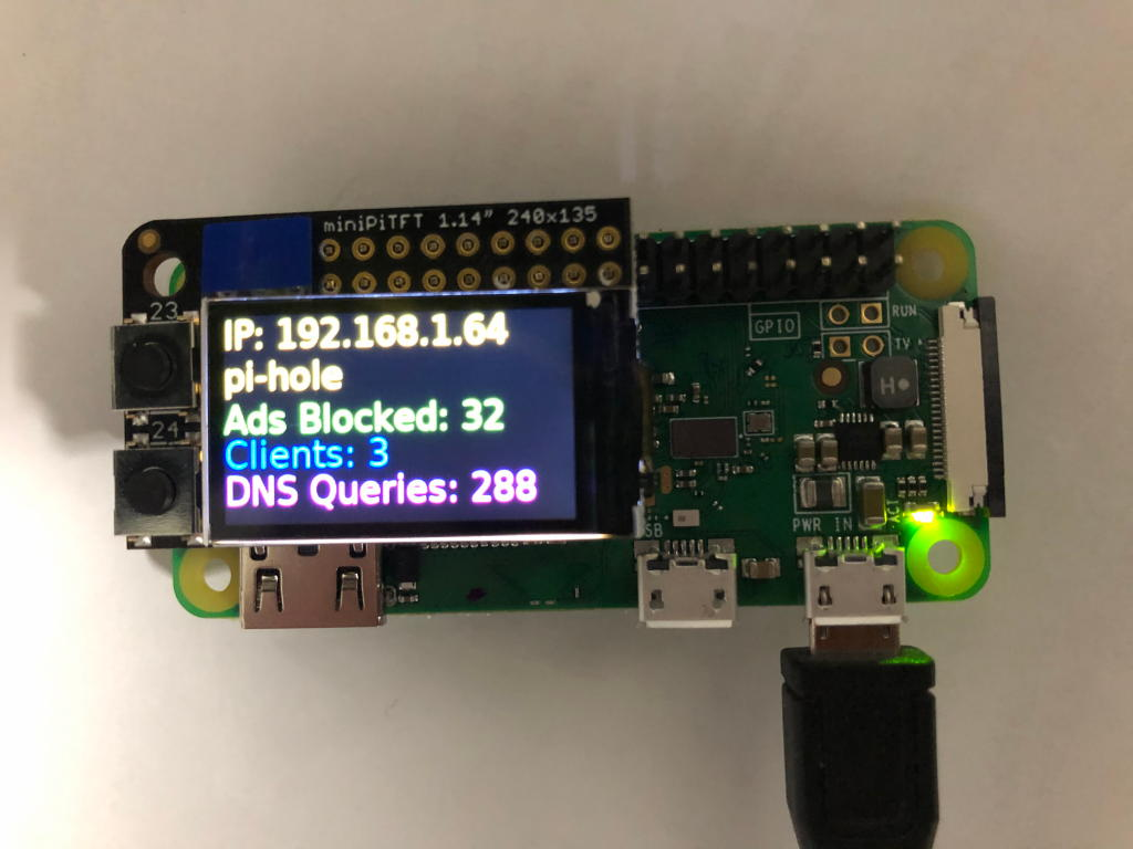 A tiny computer with an even tinier screen reporting information about Pi-Hole activity.